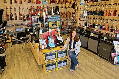 Room filled with guitars and owner Lauren.